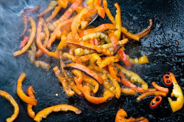 Gegrillter gerösteter paprika auf einer heißen pfanne auf offenem feuer