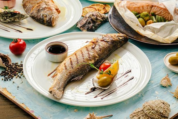 Gegrillter gourmet-wolfsbarschfisch auf dem servierten tisch