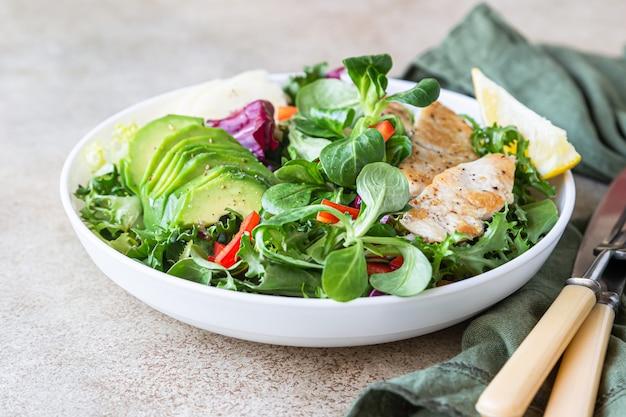 Gegrillter hähnchenbrust-, avocado-, apfel- und paprikasalat mit salatblättern mischen.