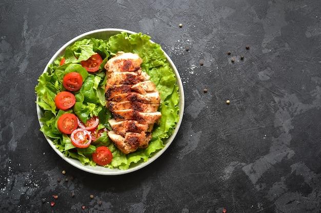 Gegrillter hähnchenbrustsalat mit spinat und tomaten.
