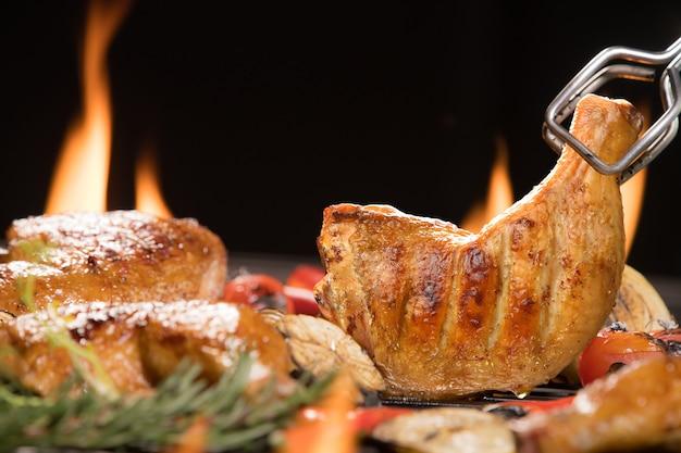 Gegrillter hähnchenschenkel mit verschiedenem gemüse auf dem brennenden grill