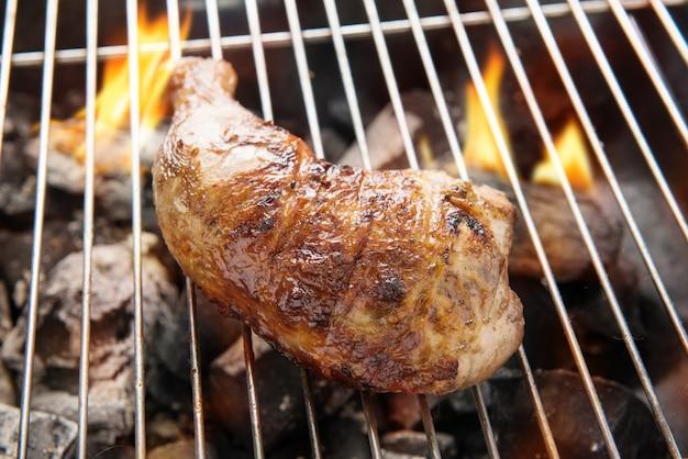 Gegrillter hähnchenschenkel über flammen auf einem grill