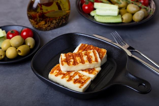 Gegrillter haloumi-käse in einer schwarzen pfanne mit oliven, tomaten, gurken und peperoni. nahansicht.
