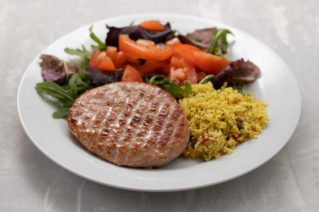 Gegrillter hamburger mit müsli und salat auf weißem teller