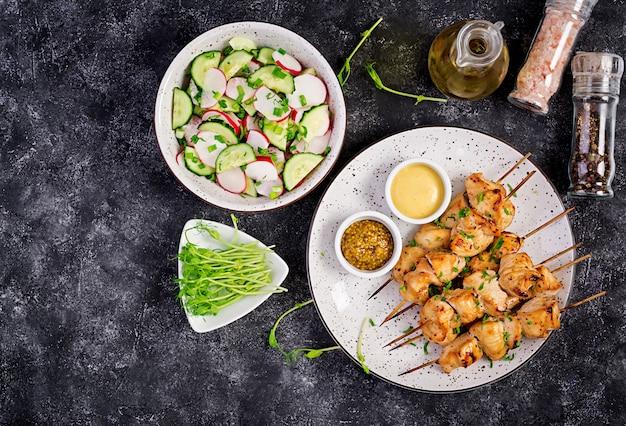 Gegrillter hühnerkebab und -salat mit gurke, rettich, zwiebel auf dunkelheit.