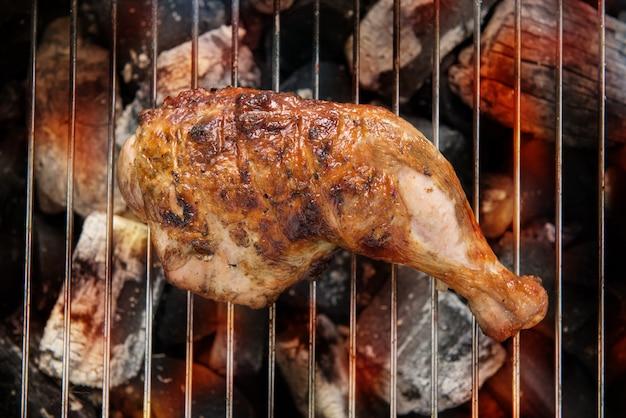 Gegrillter hühnerschenkel über flammen auf einem grill.