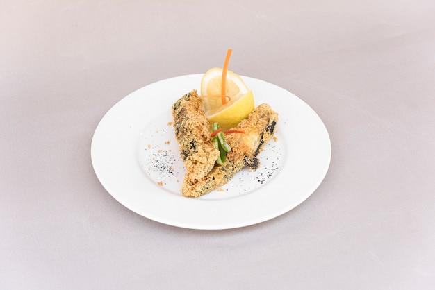 Gegrillter karpfen, serviert mit zitrone und dekoriert mit radieschen und frischen blättern, leichter hintergruß