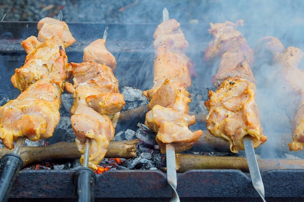 Gegrillter kebab, der auf metallaufsteckspindel kocht. gebratenes fleisch am grill gekocht.