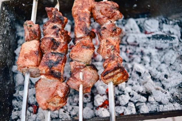 Gegrillter kebab. schweinefleischspieße werden über holzkohle gekocht. street food picknick. kebab, grill