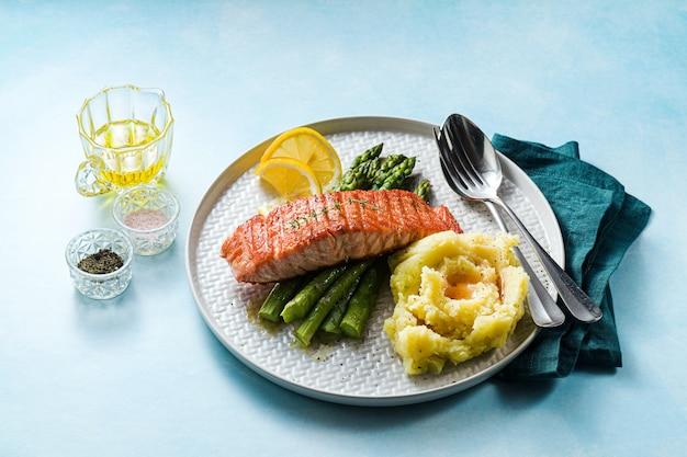 Gegrillter lachs mit frischem spargel und kartoffelpüree auf einem teller. gesundes essen auf dem tisch