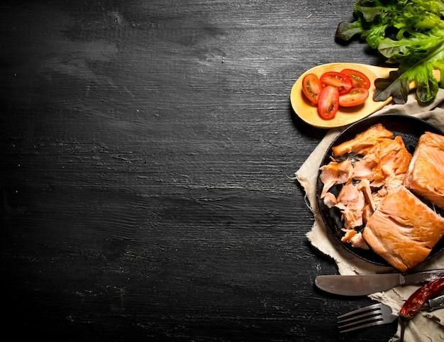 Gegrillter lachs mit tomaten und kräutern. auf der schwarzen tafel.