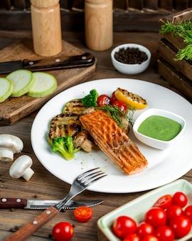 Gegrillter lachs, serviert mit gegrilltem zucchini-zitronen-tomaten-paprika-pilz und brokkoli