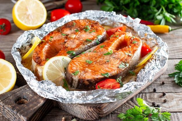 Gegrillter lachsfisch mit gewürzen und verschiedenem gemüse auf holztisch