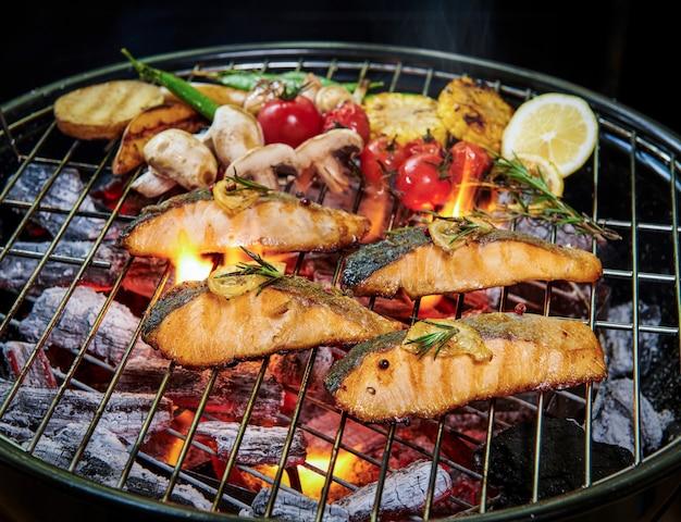 Gegrillter lachsfisch mit verschiedenem gemüse auf der pfanne auf dem brennenden grill pfeffer zitrone und salz, kräuterdekoration. selektiver fokus. gesundes essenskonzept.