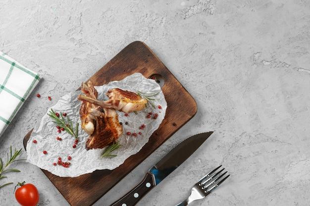 Gegrillter lammrücken serviert auf einem holzbrett. lammsteaks