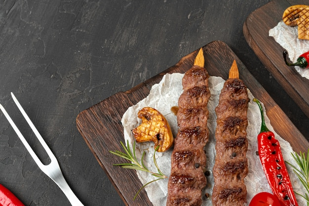 Gegrillter lula-kebab am spieß auf holzbrett