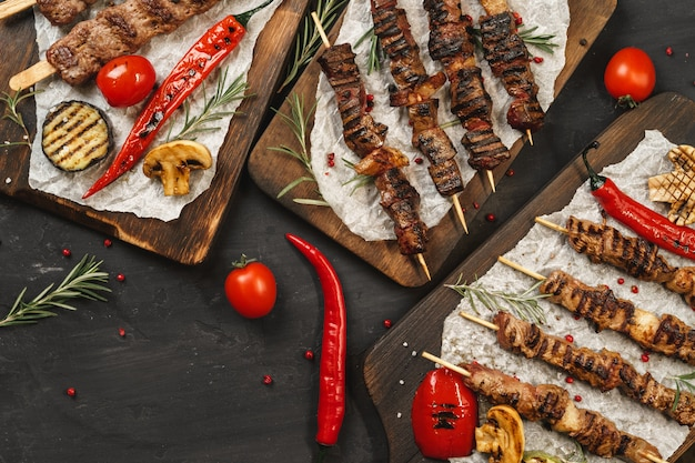 Gegrillter lula-kebab auf spießen serviert auf holzbrett, schwarzer tischhintergrund