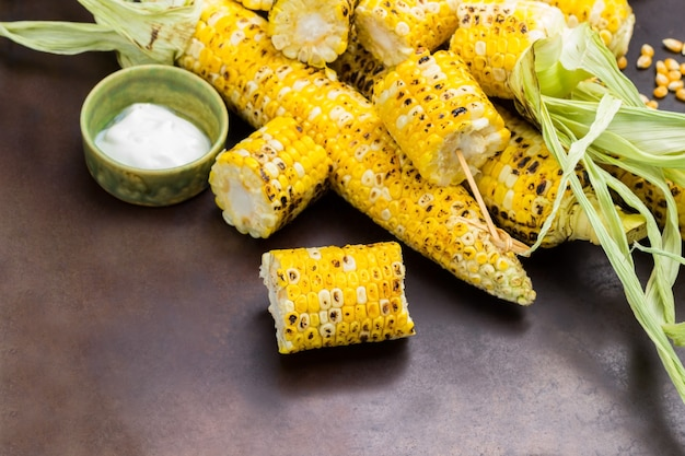 Gegrillter mais in scheiben geschnitten. gegrillte maiskolben mit blättern. rostiger hintergrund. platz kopieren. ansicht von oben