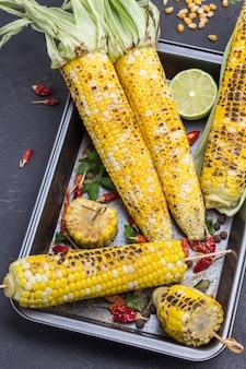 Gegrillter mais und getrocknete paprikaschoten auf palette. schwarzer hintergrund. ansicht von oben