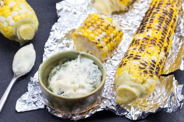 Gegrillter mais und schalen mit sauce auf folie. schwarzer hintergrund. ansicht von oben