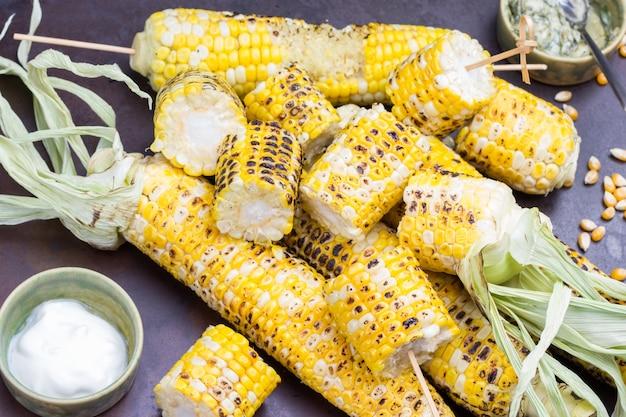 Gegrillter mais und schüsseln mit soße. maisstücke am spieß. rostiger metallhintergrund. ansicht von oben