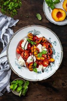 Gegrillter pfirsich-caprese-salat mit mozzarella und tomaten