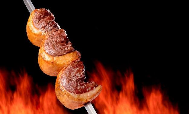 Gegrillter picanha-grill mit verschwommenem feuer im hintergrund brasilianisches essen