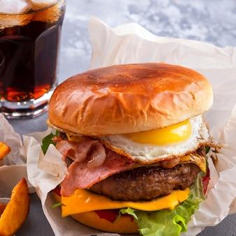 Gegrillter rindfleischburger gebratener speck und eier, käse, tomaten und kopfsalat. fast food. nahansicht