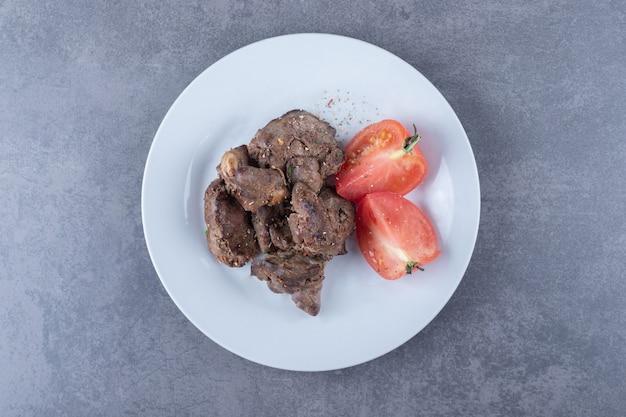 Gegrillter rindfleischkebab und tomate auf weißem teller.