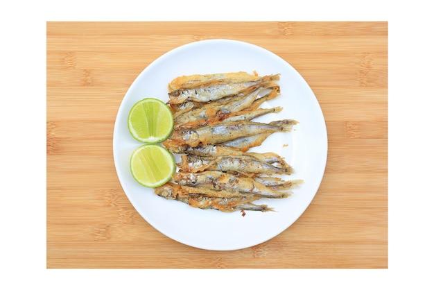 Gegrillter shishamo-fisch serviert mit zitrone und süßer soße auf holzbretthintergrund. japanisches essen von oben
