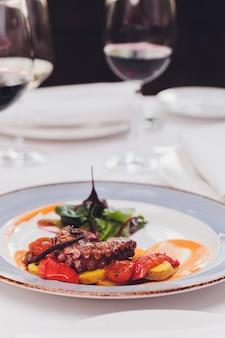 Gegrillter tintenfisch mit gemüse und tintenfischsauce. restaurant, lifestyle, reiselebensmittel - gegrillter tintenfisch mit gemüse restaurantmenü. italienische frische meeresfrüchte.