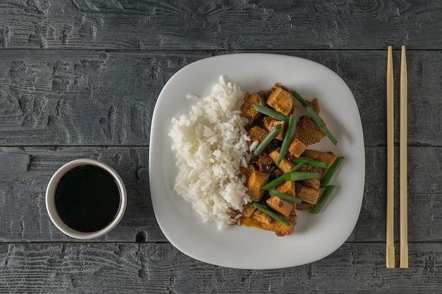 Gegrillter tofukäse mit gemüse und reis auf einem holztisch. vegetarisches asiatisches gericht. flach liegen.