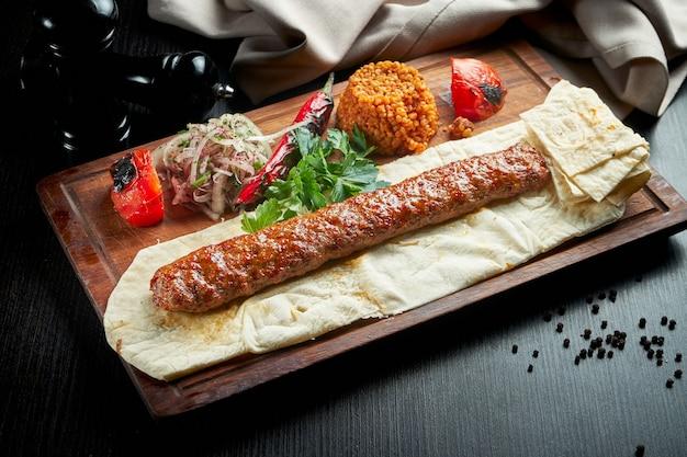 Gegrillter türkischer adana-kebab mit gegrilltem gemüse, zwiebeln und reis auf einem holzbrett. dunkler tisch.