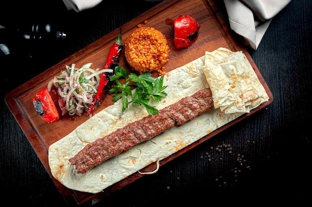 Gegrillter türkischer lamm-lula-kebab mit gegrilltem gemüse, zwiebeln und reis auf holzbrett