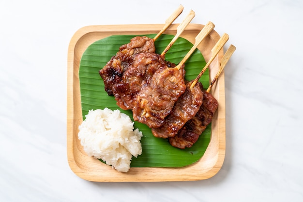 Gegrilltes aufgespießtes milchschweinefleisch mit weißem klebrigem reis
