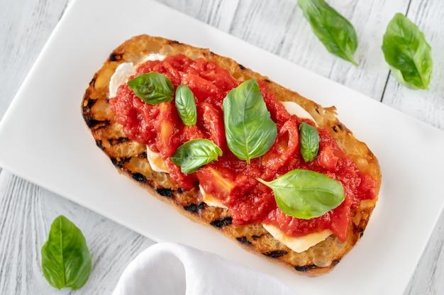 Gegrilltes brot mit mozzarella und pürierten tomaten