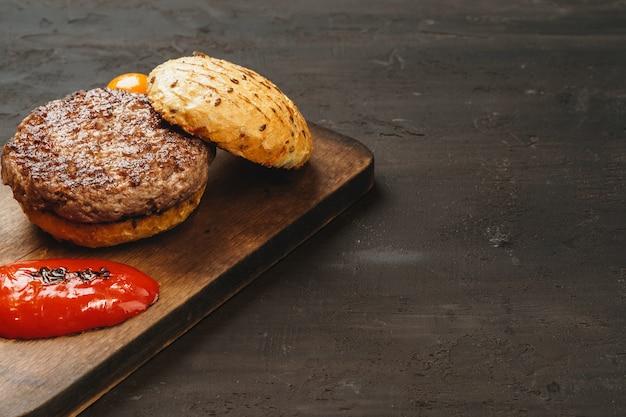 Gegrilltes burgerschnitzel mit einem brötchen auf holzbrett, draufsicht