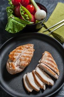 Gegrilltes chikenfilet auf der pfanne und rohes gemüse in der schüssel