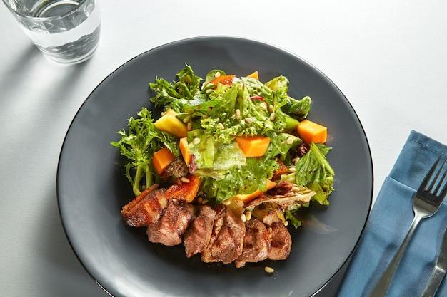 Gegrilltes entenfleisch mit geröstetem kürbis und frischem grünem salat auf einem teller mit besteck auf einem tisch