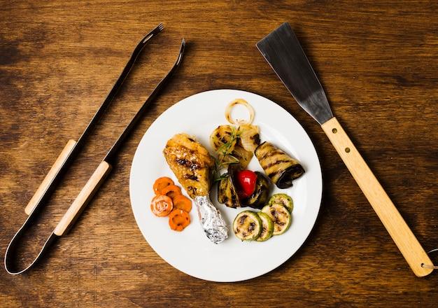 Gegrilltes essen auf teller und grillwerkzeug