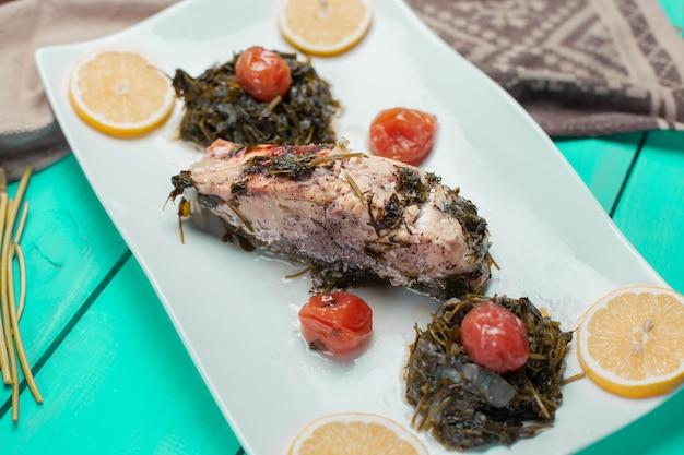 Gegrilltes fischfilet mit grünem salat und zitronenscheiben