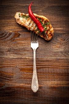Gegrilltes fleisch. auf einer gusseisernen pfanne liegen gebratene steaks zum grillen, gegrilltes gemüse, zwiebeln, kirschtomaten, champignons und paprika. schönes essen im restaurant.