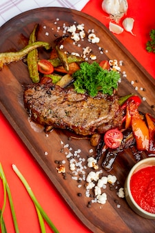 Gegrilltes fleisch mit gebratenem gemüse und kräutern