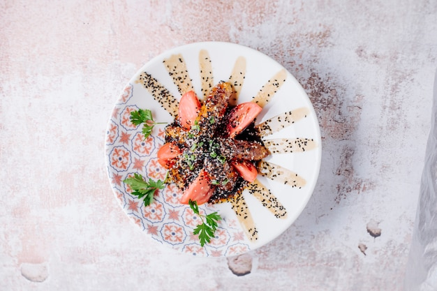 Gegrilltes fleisch mit gewürzen und tomatenscheiben in teriyaki-sauce.