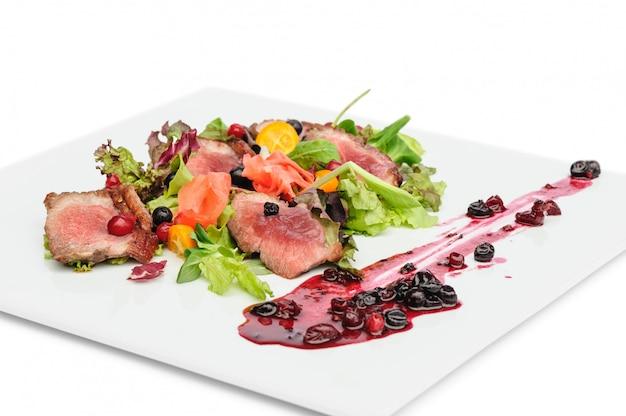 Gegrilltes fleisch mit preiselbeer-johannisbeer-sauce