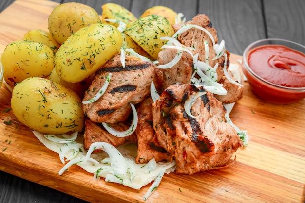 Gegrilltes fleisch mit salzkartoffeln und gemüse