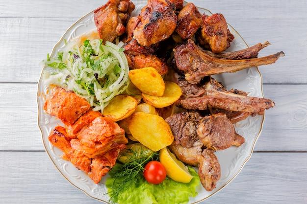 Gegrilltes fleisch, rippen, gegrillter lachsfisch, kartoffeln, kräuter und tomate auf weißer platte und weißem holztisch