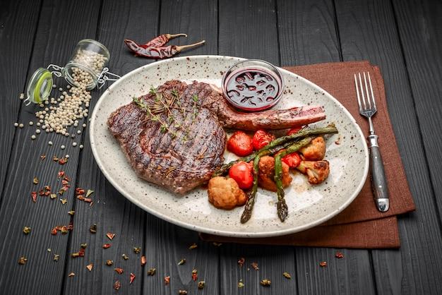 Gegrilltes fleisch und gemüse auf rustikalem holztisch