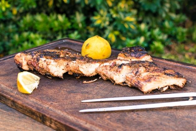 Gegrilltes fleisch und geschnittene zitrone auf tabelle