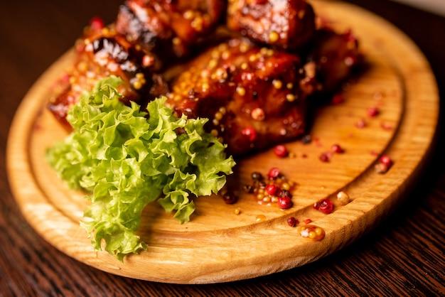 Gegrilltes fleisch und salatblätter auf holztablett